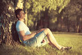 Relaxing man sitting under a tree with eyes closed meditating enjoying the warm evening sunset in profile Royalty Free Stock Photo