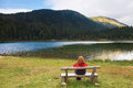 Relaxing near a mountain lake lonely woman sits on bench and watching the Stock Image