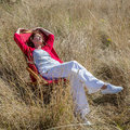 Relaxing 50s woman enjoying sun warmth alone on her deckchair Royalty Free Stock Photo