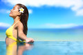 Relaxing serene woman at travel spa resort pool happy blissful asian young in bikini enjoying sun on holidays on hawaii Royalty Free Stock Images