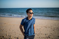 Relaxing and smiling asian young man on the beach Royalty Free Stock Photo