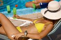 Relaxing by swimming pool sexy woman in bikini drinking cocktail face covered with straw hat Stock Images