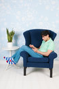 Relaxing with tablet at home young man sitting in blue armchair digital in living Royalty Free Stock Image