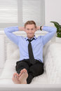 Relaxing after working day. Cheerful young businessman relaxing Royalty Free Stock Photo