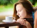 Relaxing young woman drinking cofee in a garden outdoors portrait Royalty Free Stock Photography