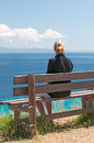 Relaxing young woman sat on a bench looking out to sea Stock Image