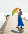 Relaxing young woman walking on the pier with umbrella Stock Photo