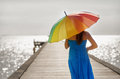 Relaxing young woman walking on the pier with umbrella Stock Image