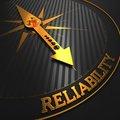 Reliability business background golden compass needle on a black field pointing to the word d render Stock Photography