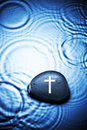 Religion cross water background a stone with a on it with and ripples Stock Image