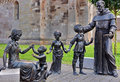 Religion statuary concept with a priest taking care of children Royalty Free Stock Photography