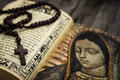 Religious concept a of a rosary and a bible on wood background Royalty Free Stock Image