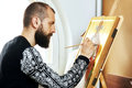 Religious painter man paints a new icon iconography with brush at workshop Royalty Free Stock Photography