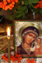 Religious still life with burning candle and an icon of the mother mary focus on the Stock Photography