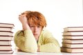 Reluctant to study portrait of redhead student looking at camera between two stacks of books Royalty Free Stock Photography