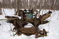 Remains of an abandoned car in the woods rusting chassis a upside down winter resembling a dragon skull Royalty Free Stock Images