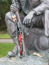 Remembrance part of a statue of a soldier on which people have left paper poppies as an act of Royalty Free Stock Photos