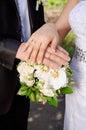Remettez les jeunes mariés avec des anneaux sur le bouquet de mariage Image stock