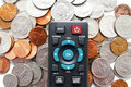 Remote control and coins Stock Photography