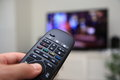 Remote control pointing at tv close up of television which is out of focus in the background Royalty Free Stock Images