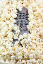 Remote control under popcorn Royalty Free Stock Photo