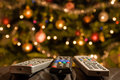 Remote controls in front of lit christmas tree Royalty Free Stock Photo