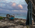 Remote Jamaican beach wth abandoned fishing boat and shirt on tree. Royalty Free Stock Photo