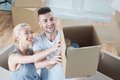 Removal is not easy thing beautiful happy couple holding big box with different colorful balls and candles in it and laughing very Stock Photography