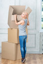 Removal is not easy thing full length portrait of lovely smiling fair haired girl wearing nice t shirt and blue jeans wanted to Stock Image