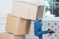 Removal is not easy thing girl wearing nice blue jeans and funny sneakers attempting to find something in the heap of boxes Stock Photos