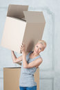 Removal is not easy thing half length portrait of beautiful smiling blonde wearing nice grey vest and holding empty box on her Stock Photo
