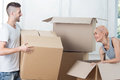 Removal is not easy thing half length portrait of lovely smiling couple standing among the boxes and going to unpack them because Royalty Free Stock Photo