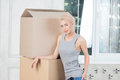 Removal is not easy thing half length portrait of sexy smiling blonde wearing grey vest and blue jeans leaning against boxes Stock Photos