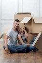 Removal is not easy thing handsome smiling dark haired guy wearing nice blue jeans sitting on the floor and embracing his lovely Stock Photo
