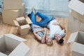 Removal is not easy thing happy smiling beautiful couple lying on the floor among the boxes and dreaming about their common future Royalty Free Stock Image