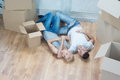 Removal is not easy thing happy smiling beautiful couple lying on the floor among the boxes and dreaming about their common future Stock Photo