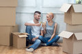 Removal is not easy thing happy smiling beautiful couple sitting on the floor among the cardboard boxes and drinking the champagne Royalty Free Stock Photo
