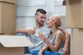 Removal is not easy thing happy smiling beautiful couple sitting on the floor among the cardboard boxes and drinking the champagne Royalty Free Stock Image