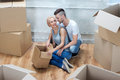 Removal is not easy thing happy smiling couple wearing nice t shirts and jeans siting on the floor near empty boxes and telling Stock Images