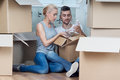 Removal is not easy thing lovely couple sitting on the floor among the boxes taking out beautiful glass vase and attentively Royalty Free Stock Image