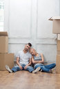 Removal is not easy thing lovely couple sitting on the floor and leaning against the wall tired because of hard Stock Image