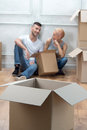 Removal is not easy thing selected focus on the big cardboard empty box lying on the floor lovely smiling couple holding the box Stock Images