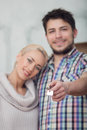 Removal is not easy thing selected focus on keys of the new house smiling happy couple on background Stock Photography