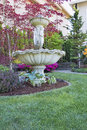 Renaissance water fountain in front lawn on landscaping with trees and flowering shrubs Royalty Free Stock Photo