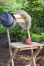 Rendezvous in the garden on a chair feminine hat men s hat and rose Stock Image