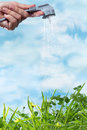 Renewable energy electrical plug watering a green grass meadow as a symbol of green and Stock Photo