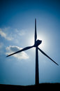 Renewable energy huge wind turbine backlit by the sun and subtly colorized for dramatic effect Stock Images