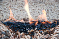 Renewable energy pine pellets in flames selective focus on the heap Stock Photos