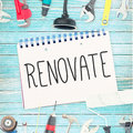 Renovate against tools and notepad on wooden background the word Royalty Free Stock Photo