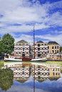 Renovated monumental mansion with white moored boat reflected in canal, Gouda, netherlands Royalty Free Stock Photo